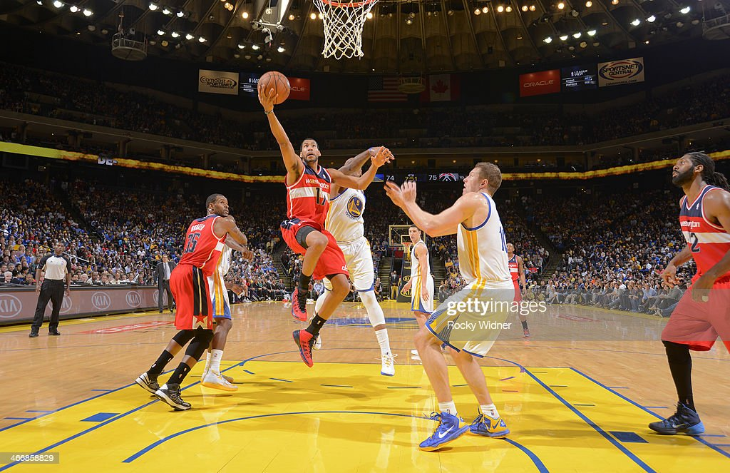 Garrett Temple of the Washington Wizards shoots a layup against David Lee and Marreese Speights of the Golden State Warriors on January 28 2014 at...