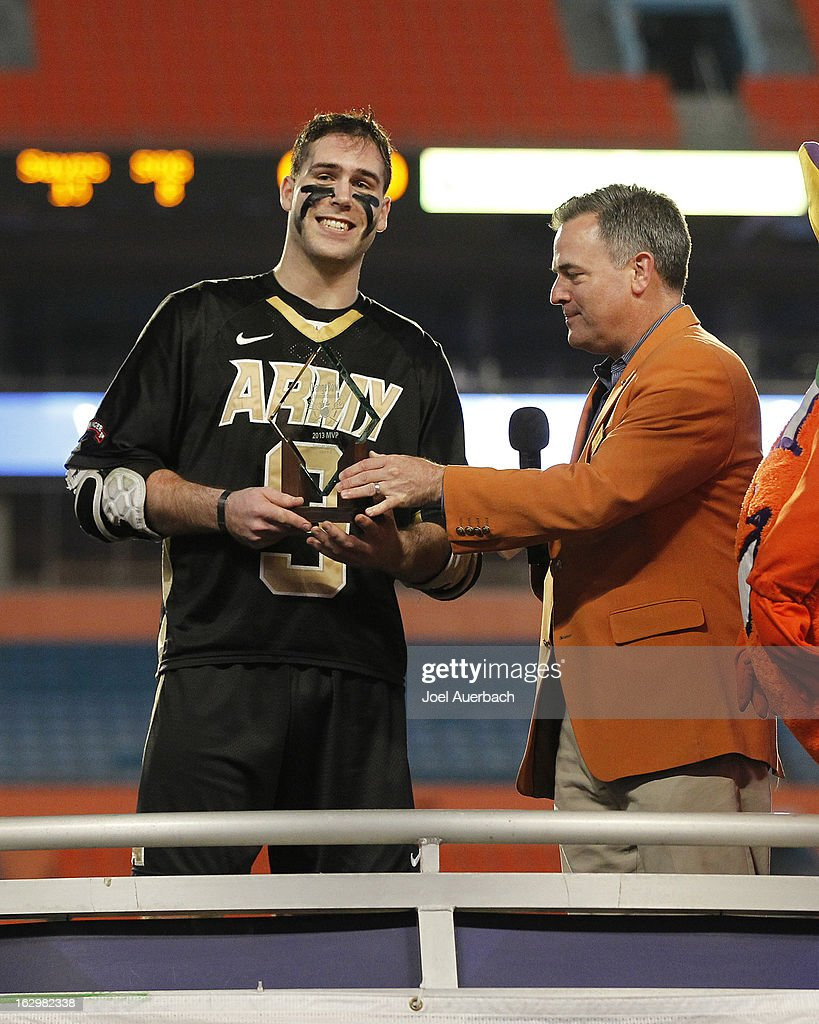 Garrett Thul #9 of the Army Black Knights is presented with the MVP trophy by Orange Bowl member Bradley Houser for scoring seven goal in the game against the Michigan Wolverines during the 2013 Orange Bowl Lacrosse Classic on March 2, 2013 at SunLife Stadium in Miami Gardens, Florida.
