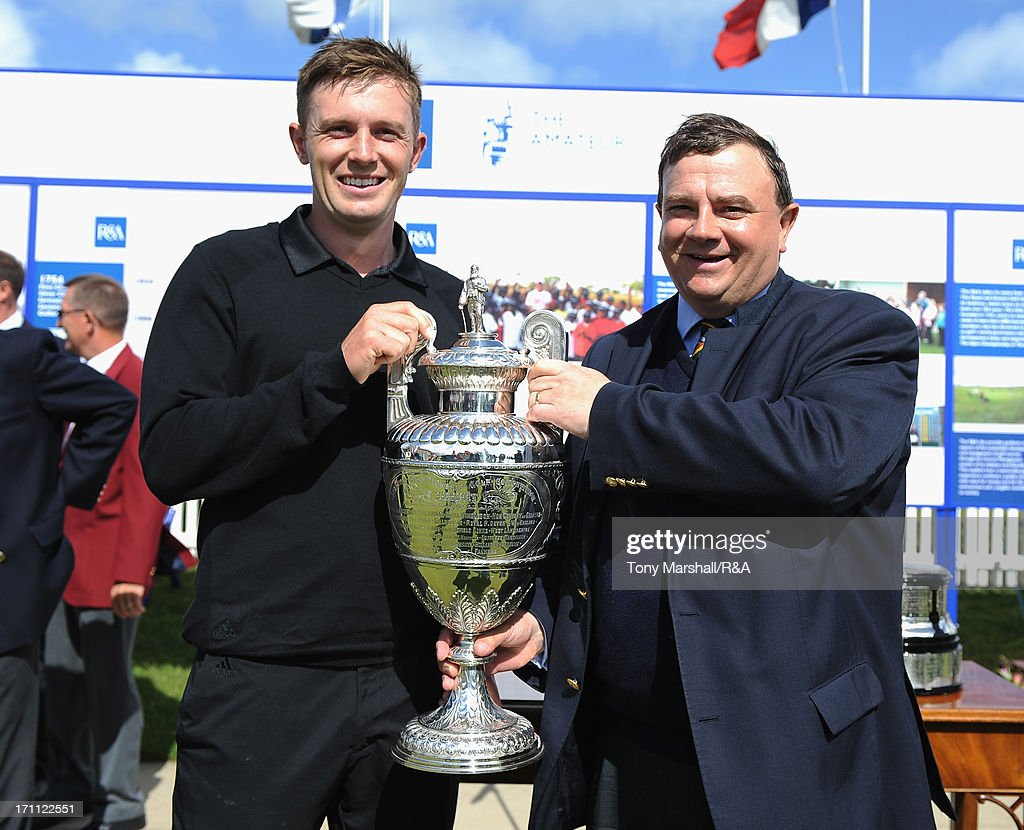 Garrick Porteous of Bamburgh Castle is presented with the trophy by Nick Owen, Captain of Royal Cinque Ports Golf Club after winning the final of The Amateur Championship at Royal Cinque Ports Golf Club on June 22, 2013 in Deal, England.