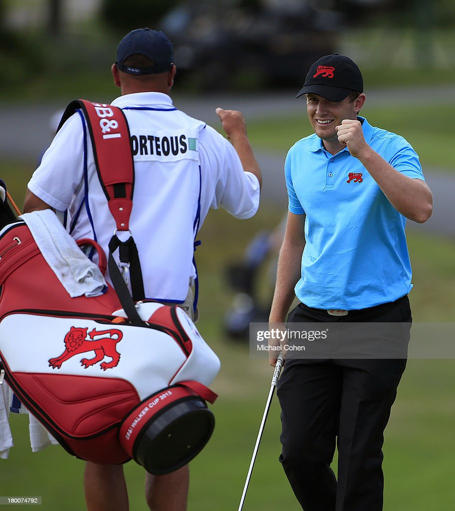 Garrick Porteous of England and the Great Britain and Ireland team celebrates with his caddie Andy Rodriguez after holing out for eagle on the first hole during the afternoon singles matches on Day Two of the 2013 Walker Cup at National Golf Links of America on September 8, 2013 in Southampton, New York.