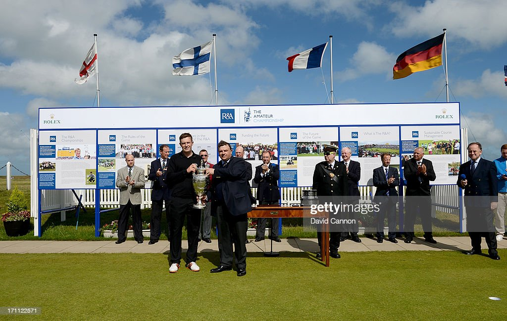 Garrick Porteous of England is presented with the Amateur Championship Trophy after his 6&5 victory in the final against Toni Hakula of Finland by the captain of Royal Cinque Ports Golf Club Nick Owen during the 2013 Amateur Championship at Royal Cinque Ports Golf Club on June 22, 2013 in Deal, England.
