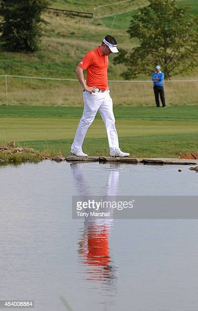 Garrick Porteous of England walks across the stepping stones over the lake on the 17th fairway during day three of DD REAL Czech Masters at Albatross...