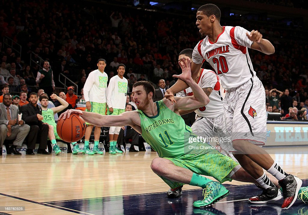 Garrick Sherman #11 of the Notre Dame Fighting Irish reaches to attempt to save a ball from going out of bounds against Wayne Blackshear #20 of the Louisville Cardinals during the semifinals of the Big East Men's Basketball Tournament at Madison Square Garden on March 15, 2013 in New York City.