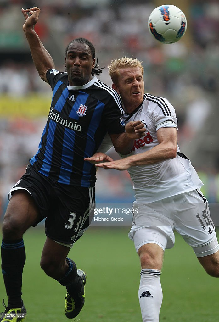 Garry Monk (R) of Swansea City tussles with Cameron Jerome (L) of Stoke City during the Barclays Premier League match between Swansea City and Stoke City at the Liberty Stadium on October 2, 2011 in Swansea, Wales.
