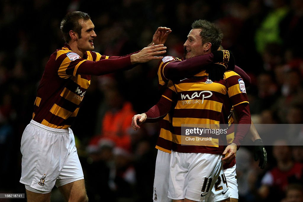 Garry Thompson (R) of Bradford is congratulated by teammate James Hanson (L) after scoring the oipening goal during the Capital One Cup quarter final match between Bradford City and Arsenal at the Coral Windows Stadium, Valley Parade on December 11, 2012 in Bradford, England.