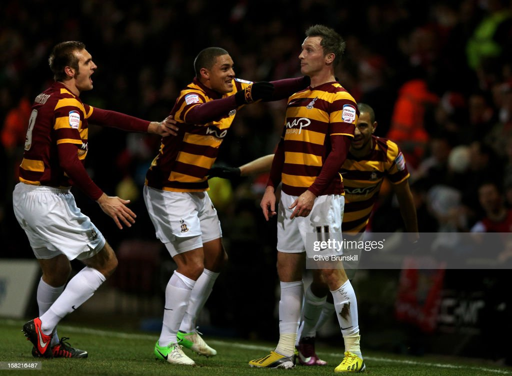 Garry Thompson (R) of Bradford is congratulated by teammates after scoring the oipening goal during the Capital One Cup quarter final match between Bradford City and Arsenal at the Coral Windows Stadium, Valley Parade on December 11, 2012 in Bradford, England.
