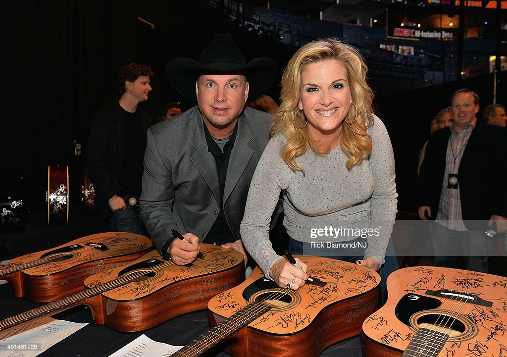 <a gi-track='captionPersonalityLinkClicked' href=/galleries/search?phrase=Garth+Brooks&family=editorial&specificpeople=206288 ng-click='$event.stopPropagation()'>Garth Brooks</a> and <a gi-track='captionPersonalityLinkClicked' href=/galleries/search?phrase=Trisha+Yearwood&family=editorial&specificpeople=216434 ng-click='$event.stopPropagation()'>Trisha Yearwood</a> sign guitars backstage during rehearsals for Playin' Possum! The Final No Show Tribute To George Jones at Bridgestone Arena on November 22, 2013 in Nashville, Tennessee.