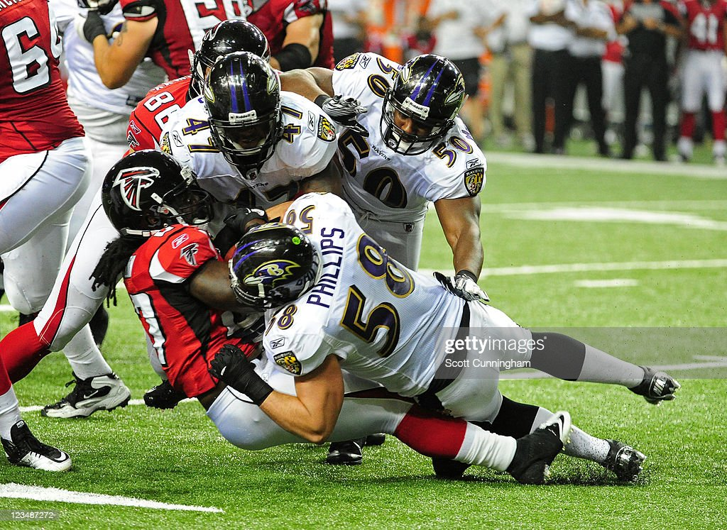 Gartrell Johnson #27 of the Atlanta Falcons is tackled by Jason Phillips #58, Chavis Williams #47, and Albert McClellan #50 of the Baltimore Ravens during a preseason game at the Georgia Dome on September 1, 2011 in Atlanta, Georgia.