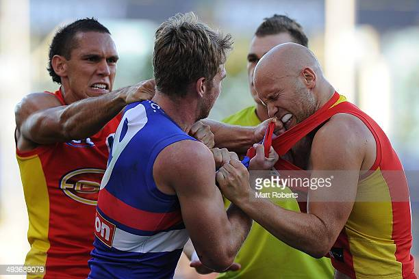 Gary Ablett and Harley Bennell of the Suns wrestle with Jake Stringer of the Bulldogs during the round 10 AFL match between the Gold Coast Suns and...
