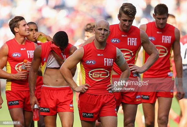 Gary Ablett and his Suns team mates look dejected as they leave the field after losing the round one AFL match between the Melbourne Demons and the...