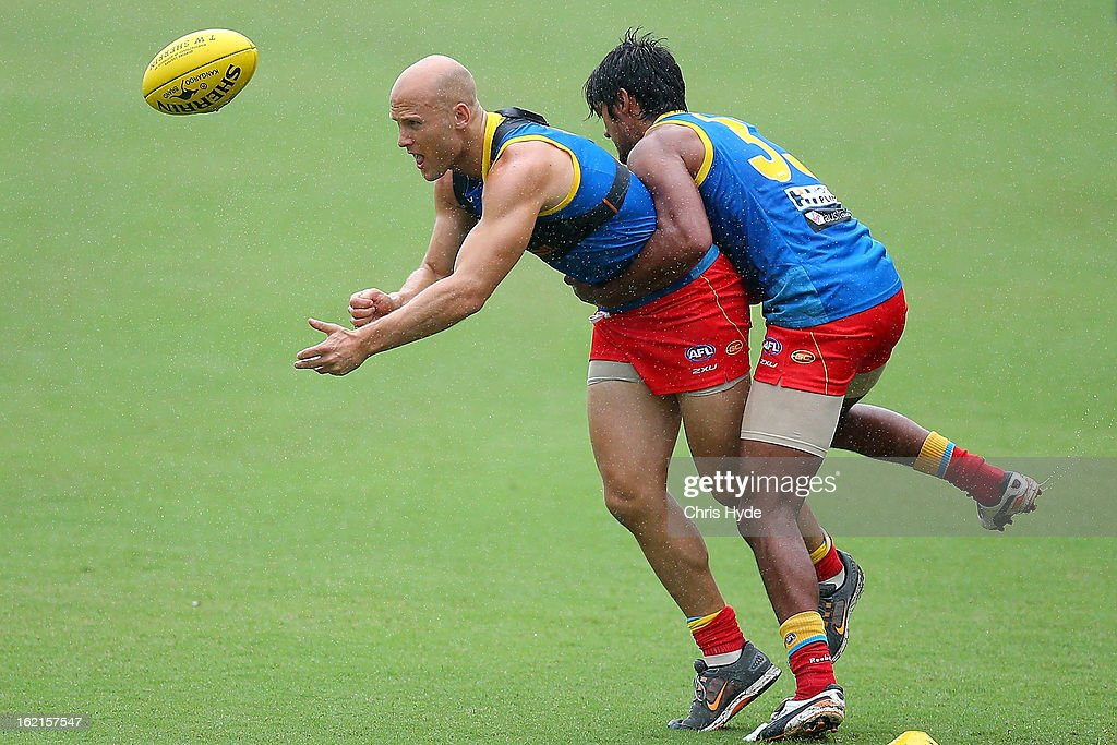 <a gi-track='captionPersonalityLinkClicked' href=/galleries/search?phrase=Gary+Ablett&family=editorial&specificpeople=206196 ng-click='$event.stopPropagation()'>Gary Ablett</a> handballs while tackled by Aaron Hall during a Gold Coast Suns AFL training session at Metricon Stadium on February 20, 2013 in Gold Coast, Australia.