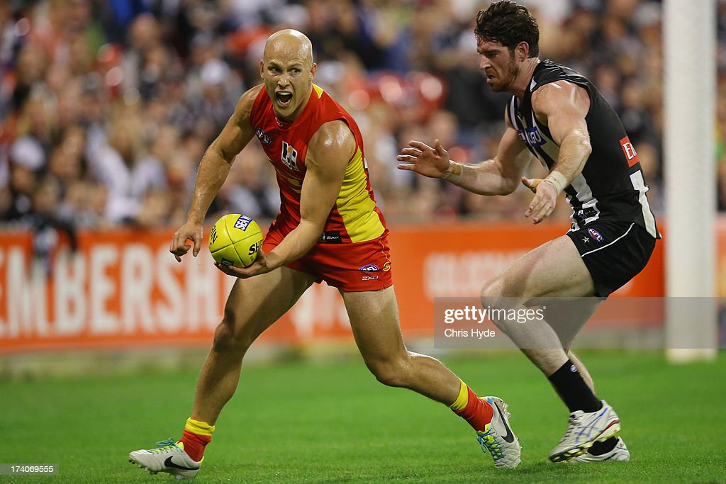 <a gi-track='captionPersonalityLinkClicked' href=/galleries/search?phrase=Gary+Ablett&family=editorial&specificpeople=206196 ng-click='$event.stopPropagation()'>Gary Ablett</a> of the Suns handballs away from Tyson Goldsack of the Magpies during the round 17 AFL match between the Gold Coast Suns and the Collingwood Magpies at Metricon Stadium on July 20, 2013 in Gold Coast, Australia.