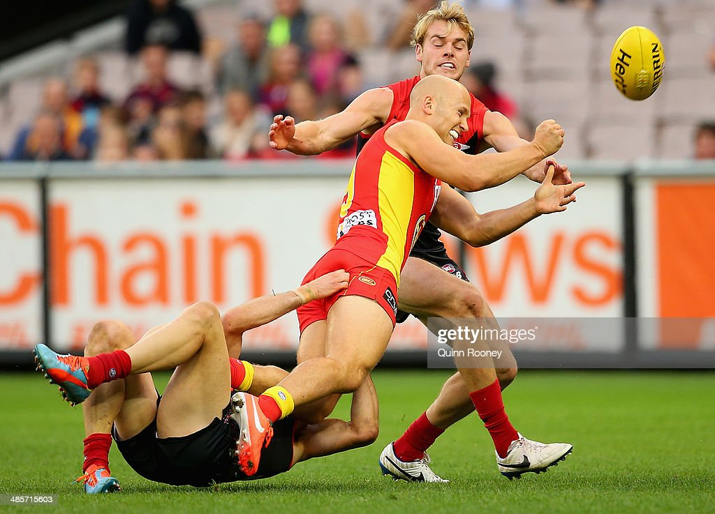 <a gi-track='captionPersonalityLinkClicked' href=/galleries/search?phrase=Gary+Ablett&family=editorial&specificpeople=206196 ng-click='$event.stopPropagation()'>Gary Ablett</a> of the Suns handballs whilst being tackled by Daniel Cross of the Demons during the round five AFL match between the Melbourne Demons and the Gold Coast Suns at Melbourne Cricket Ground on April 20, 2014 in Melbourne, Australia.