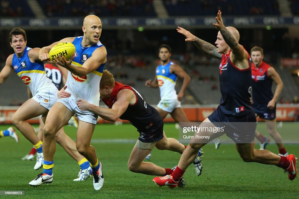 Gary Ablett of the Suns handballs whilst being tackled during the round seven AFL match between the Melbourne Demons and the Gold Coast Suns at Melbourne Cricket Ground on May 12, 2013 in Melbourne, Australia.