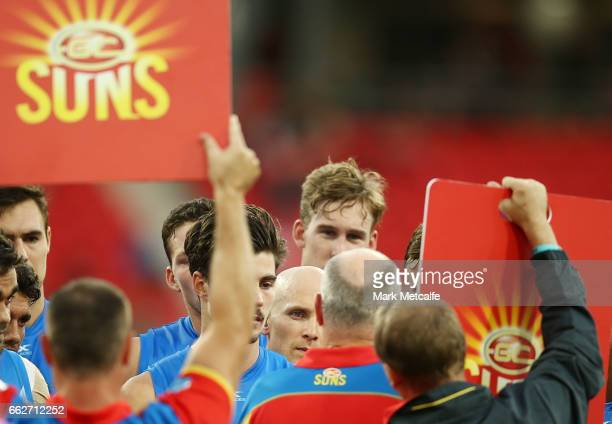 Gary Ablett of the Suns looks on as Suns head coach Rodney Eade gives a three quarter time team talk during the round two AFL match between the...