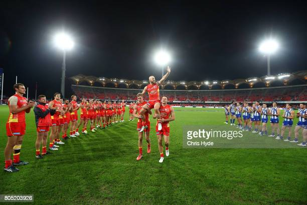 Gary Ablett of the the Suns is chaired from the field after playing his 300th match during the round 15 the Gold Coast Suns and the North Melbourne...
