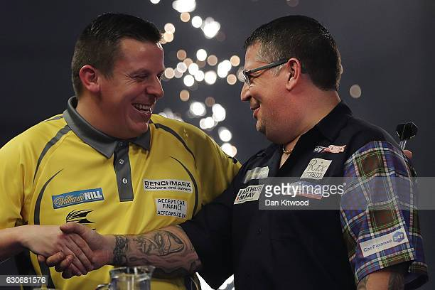 Gary Anderson from Scotland shakes hands with his opponent Dave Chisnall after defeating him in the quarter finals of the 2016 William Hill World...