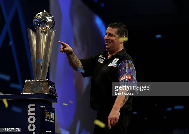 Gary Anderson of Scotland celebrates with the Sid Waddell trophy after defeating Phil Taylor of England in the final of the 2015 William Hill PDC...