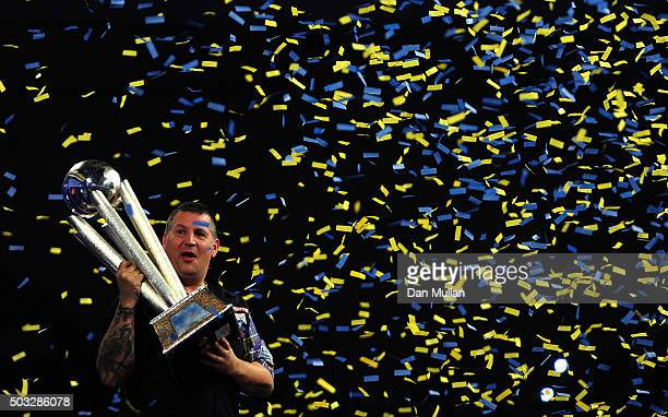 Gary Anderson of Scotland celebrates with the Sid Waddell Trophy after victory over Adrian Lewis of England in the final match during Day Fifteen of...
