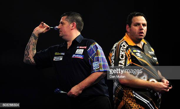 Gary Anderson of Scotland throws as Adrian Lewis of England looks on during the final match on Day Fifteen of the 2016 William Hill PDC World Darts...