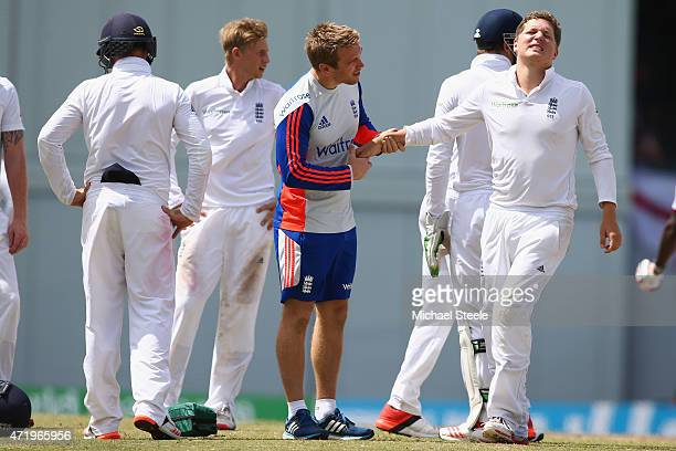 Gary Ballance of England is treated by physio Craig de Weymarn after being hit on the hand whilst fielding at silly mid onshort leg during day two of...