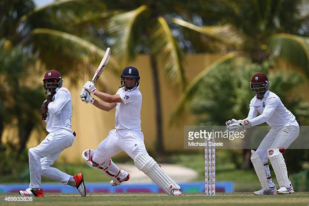 Gary Ballance of England plays to the offside as wicketkeeper Denesh Ramdin and Jermaine Blackwood look on during day four of the 1st Test match...