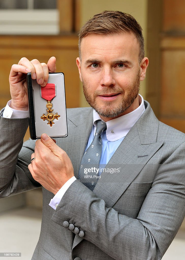 <a gi-track='captionPersonalityLinkClicked' href=/galleries/search?phrase=Gary+Barlow&family=editorial&specificpeople=616384 ng-click='$event.stopPropagation()'>Gary Barlow</a> holds his OBE, for services to the entertainment industry and to charity, which was awarded to him by Queen Elizabeth II during an Investiture ceremony at Buckingham Palace on November 21, 2012 in London, England.