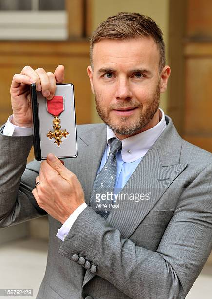 Gary Barlow holds his OBE for services to the entertainment industry and to charity which was awarded to him by Queen Elizabeth II during an...