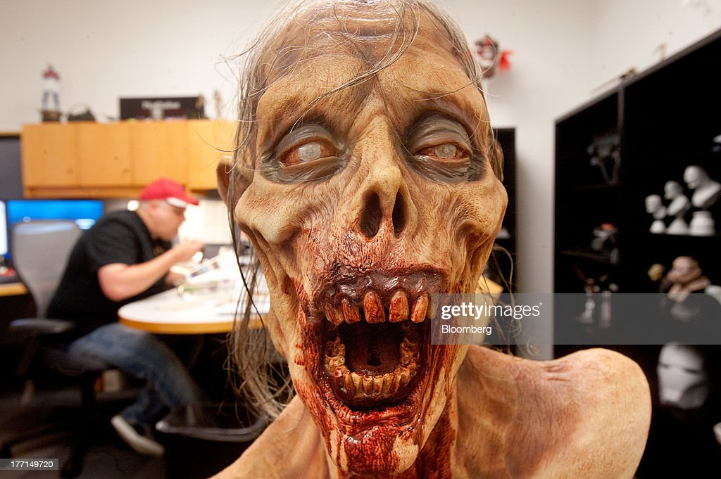 Gary Barth, senior manager of fabrication arts and design, left, eats lunch behind a zombie bust at Sony Computer Entertainment America's headquarters in San Mateo, California, U.S., on Tuesday, Aug. 20, 2013. Sony Corp. will start selling the PlayStation 4 in North America on Nov. 15, moving to obtain an early advantage in the largest video-game market against Microsoft Corp. Photographer: Noah Berger/Bloomberg via Getty Images *
