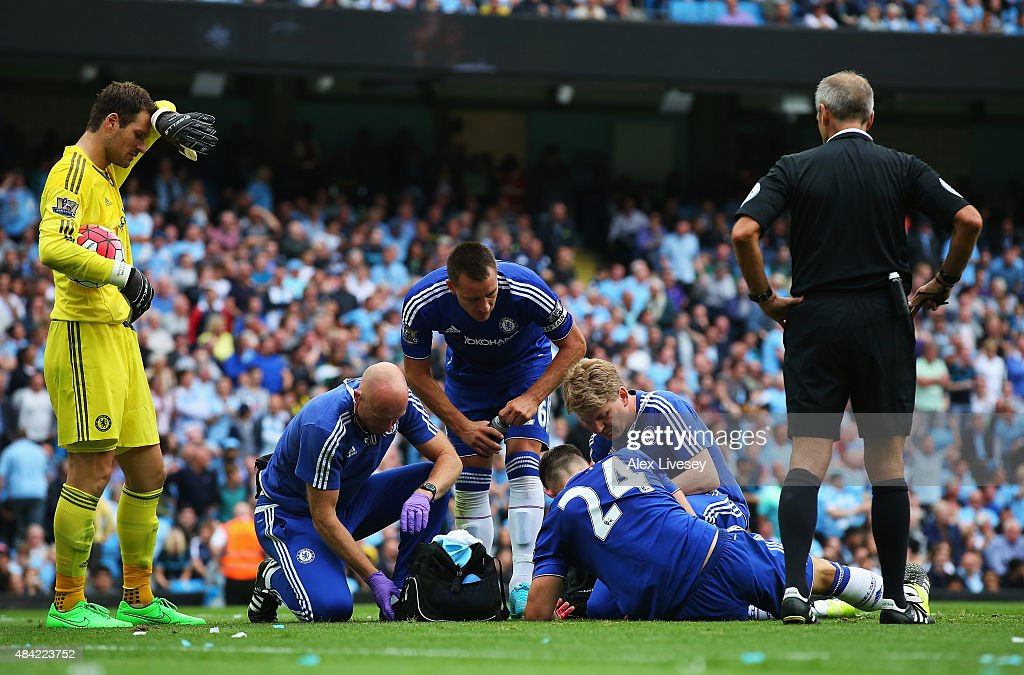 Gary Cahill of Chelsea receives treatment from the new Chelsea medical team during the Barclays Premier League match between Manchester City and Chelsea at the Etihad Stadium on August 16, 2015 in Manchester, England.