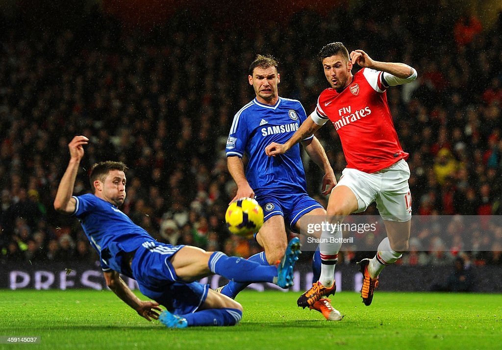 Gary Cahill of Chelsea tackles Olivier Giroud of Arsenal during the Barclays Premier League match between Arsenal and Chelsea at Emirates Stadium on December 23, 2013 in London, England.