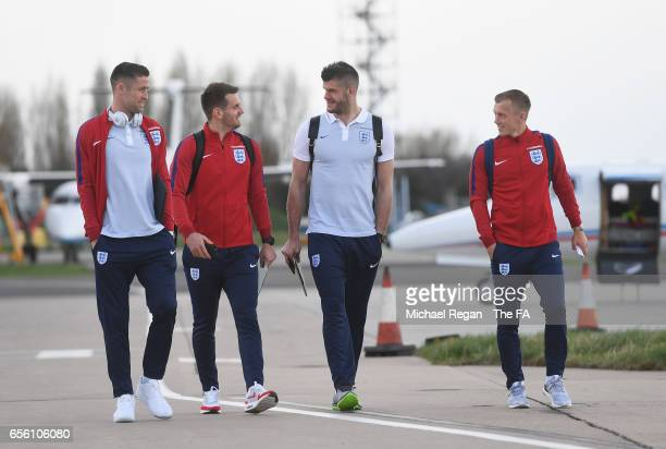 Gary Cahill Tom Heaton Fraser Forster and James WardProwse of England walk to the plane as they leave for the International Friendly match against...
