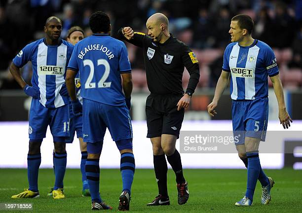 Gary Caldwell and Jean Beausejour of Wigan Athletic complain to referee Anthony Taylor following the award of a penalty during the Barclays Premier...