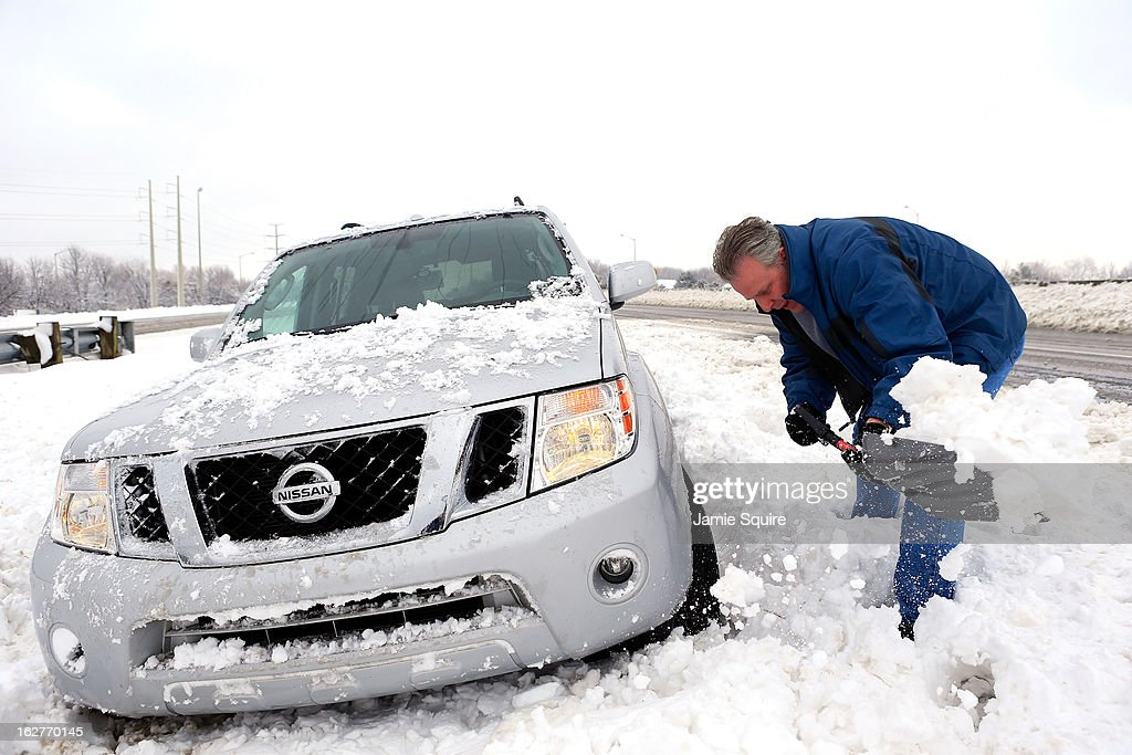 Gary Cook digs his car out after sliding off the interstate after the area is hit by a snowstorm on February 26, 2013 in Overland Park, Kansas. This is the second major snowstorm the midwest has seen this week dropping a half-foot or more of snow across Missouri and Kansas and cutting power to thousands...