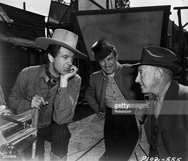 Gary Cooper talks to costar Robert Preston and film director Cecil B DeMille on the set of the western adventure film 'NorthWest Mounted Police' 1940
