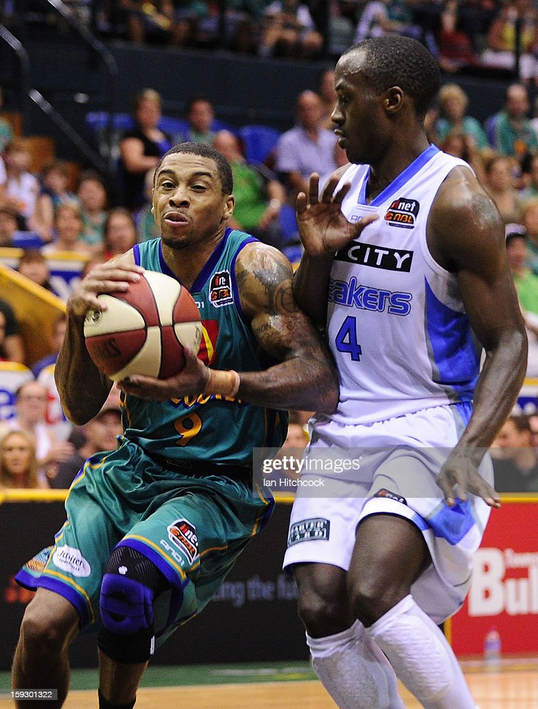 Gary Ervin of the Crocodiles attempts to drive past Cedric Jackson of the Breakers during the round 14 NBL match between the Townsville Crocodiles and the New Zealand Breakers at Townsville Entertainment Centre on January 11, 2013 in Townsville, Australia.