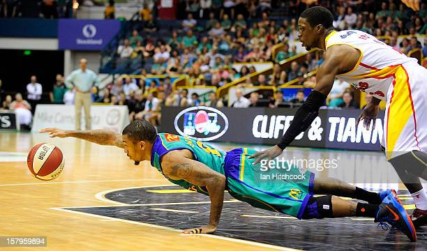Gary Ervin of the Crocodiles dives for the ball past Jonny Flynn of the Tigers during the round ten NBL match between the Townsville Crocodiles and...