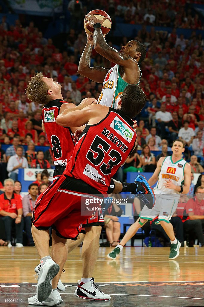 Gary Ervin of the Crocodiles lays up against Rhys Carter of the Wildcats during the round 16 NBL match between the Perth Wildcats and the Townsville Crocodiles at Perth Arena on January 25, 2013 in Perth, Australia.
