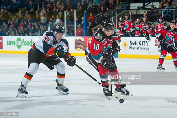 Gary Haden of the Medicine Hat Tigers stick checks Nick Merkley of the Kelowna Rockets during third period at Prospera Place on November 5 2016 in...