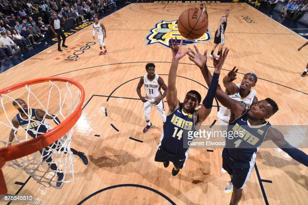 Gary Harris and Paul Millsap of the Denver Nuggets go up for a rebound against the New Orleans Pelicans on November 17 2017 at the Pepsi Center in...