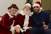 Gary Harris of the Denver Nuggets visits kids and poses for a photo with Santa and Mrs Claus at the Vickers Boys Girls Club during the NBA 'Season of...