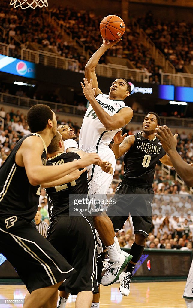 Gary Harris #14 of the Michigan State Spartans gets off a second half shot between Terone Johnson #0 and D.J. Byrd #21 of the Purdue Boilermakers at the Jack T. Breslin Student Events Center on January 5, 2013 in East Lansing, Michigan. Michigan State won the game 84-61.
