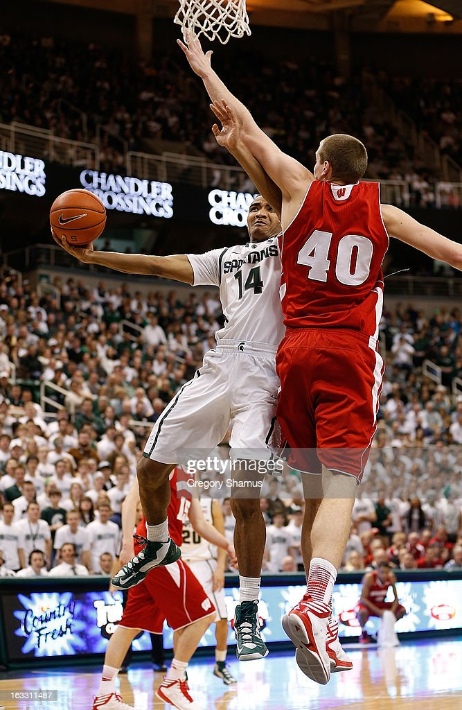 Gary Harris #14 of the Michigan State Spartans tries to get a second half shot off around Jared Berggren #40 of the Wisconsin Badgers at the Jack T. Breslin Student Events Center on March 7, 2013 in East Lansing, Michigan. Michigan State won the game 58-43.