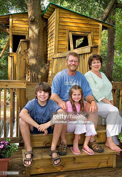 Gary Hatley top center with his wife Debra right and children Jack left and Sarah sit in front of the tree house that extends off the backyard deck...