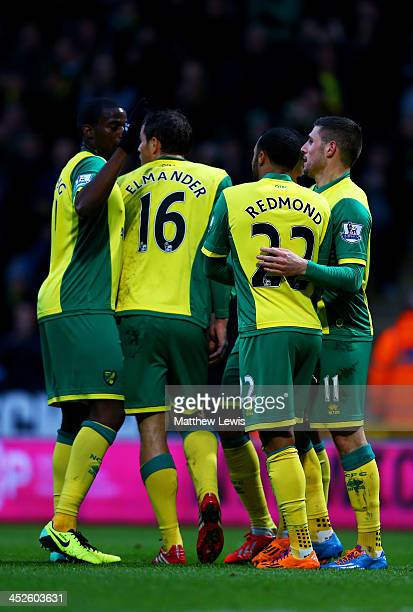 Gary Hooper of Norwich is congratulated by teammates after scoring the opening goal during the Barclays Premier league match between Norwich City and...