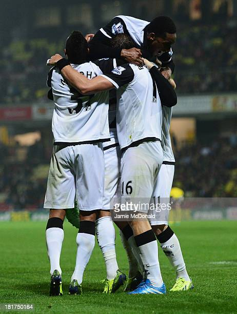 Gary Hooper of Norwich City celebrates with team mates as he scores their third goal during the Capital One Cup Third Round match between Watford and...