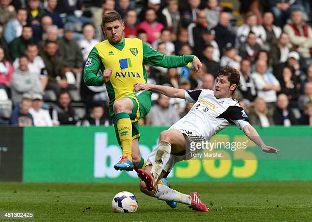 Gary Hooper of Norwich City is tackled by Ben Davies of Swansea City during the Barclays Premier League match between Swansea City and Norwich City...