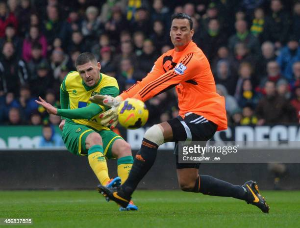Gary Hooper of Norwich shots past Michael Vorm of Swansea but misses the goal during the Barclays Premier League match between Norwich City and...
