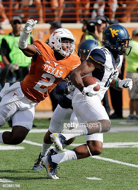 Gary Jennings of the West Virginia Mountaineers runs with the ball as Kris Boyd of the Texas Longhorns attempts to stop him at Darrell K Royal Texas...