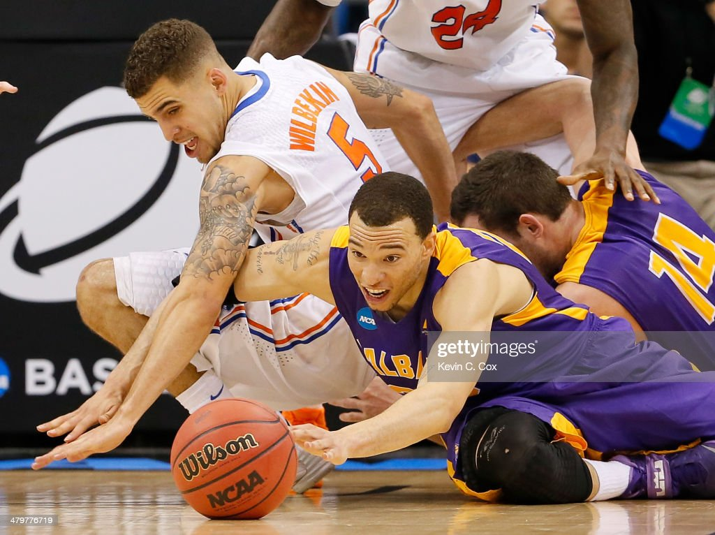 Gary Johnson of the Albany Great Danes and Scottie Wilbekin of the Florida Gators go after a loose ball in the second half during the second round of...